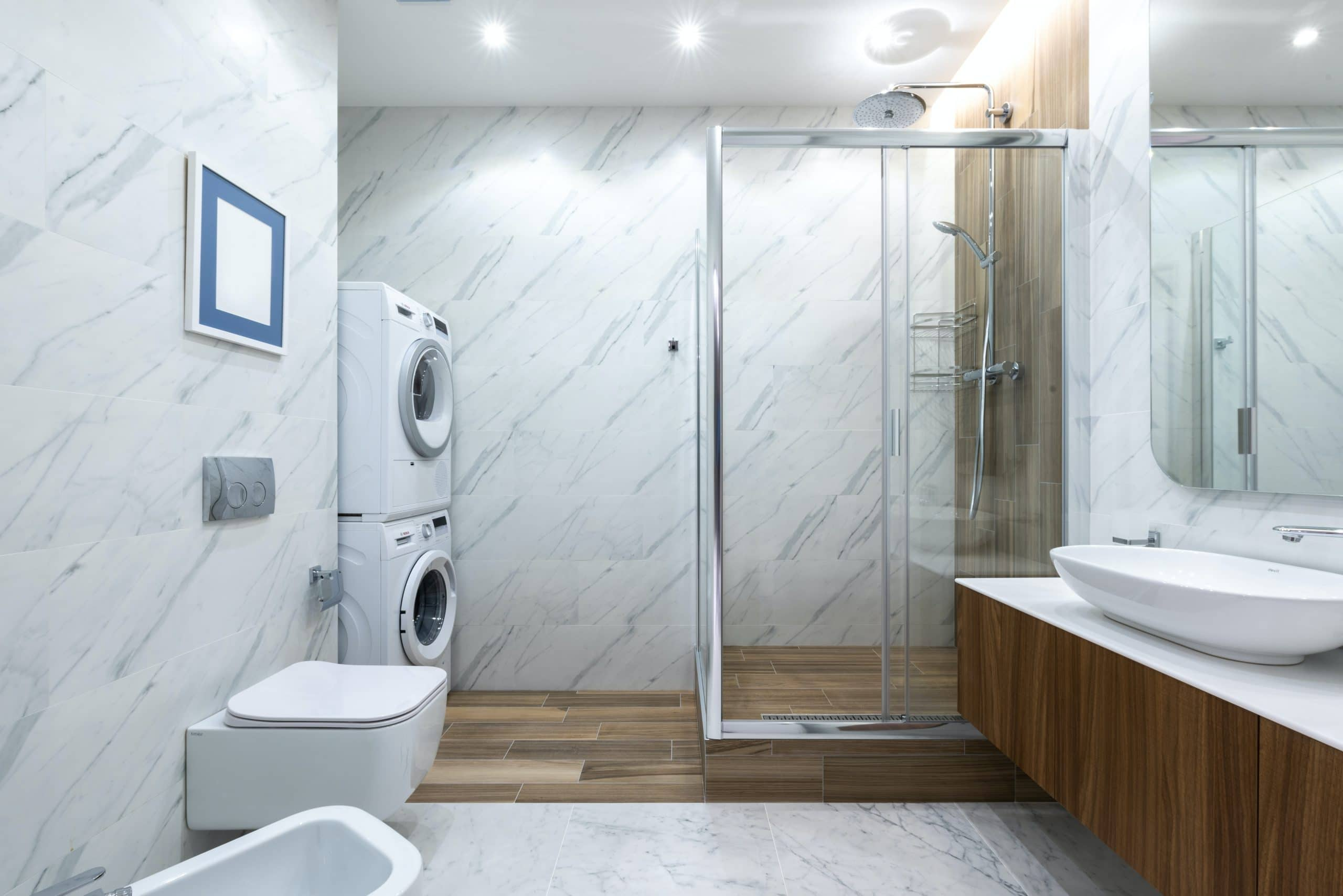 Contemporary bathroom toilet near tiled wall against cabinet with sink placed near shower cabin with glass wall and washing machines