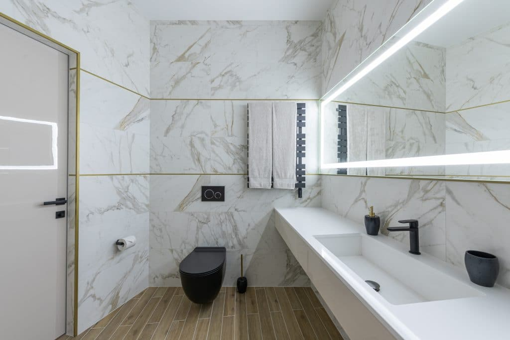 Interior of contemporary bathroom with marble walls and ceramic sink in modern minimalist apartment