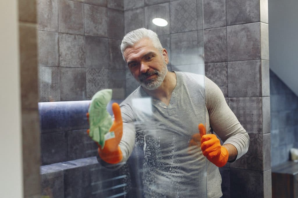 Grey haired male with beard in orange rubber gloves attentively cleaning shower glass in bathroom