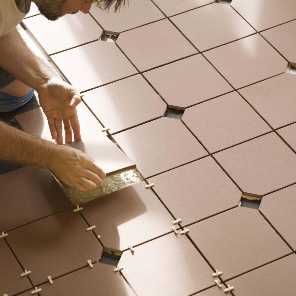 Person installing tiles in bathroom